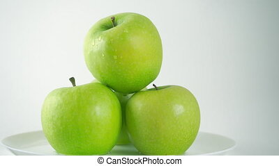 Green apples on plate and dripping water against white...
