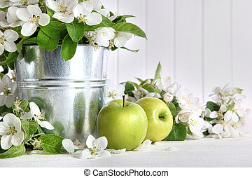 Green apples with blossoms on table