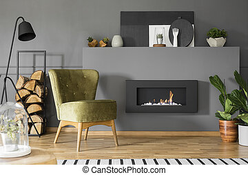 Green armchair and black lamp next to fireplace in grey living room interior with plants. Real photo