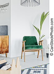 Green armchair in white room