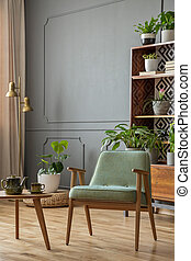 Green armchair next to wooden table in grey vintage living room interior with plants. Real photo