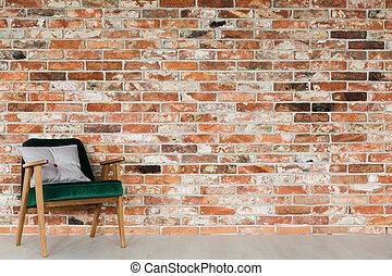 Green armchair on brick wall