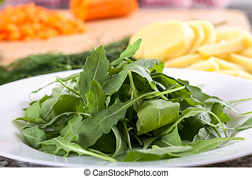 Close up of green arugula on white plate