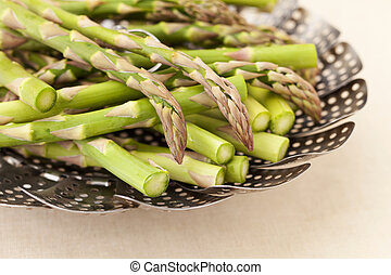 green asparagus in steamer basket - green fresh asparagus in...
