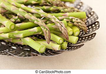 green asparagus in steamer basket - green fresh asparagus in...