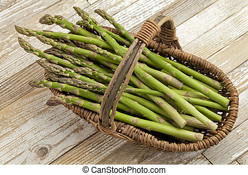 green asparagus in wicker basket on grunge white painted wood background