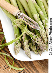 Green Asparagus On A Plate Beeing Peeled