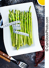 green asparagus on white plate and on a table