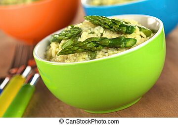 Green asparagus risotto in colorful bowls (Selective Focus,...