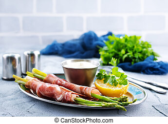 green asparagus with bacon on a table