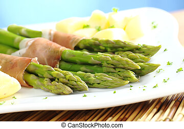 Green asparagus with ham and potatoes (Selective Focus, Focus on the asparagus heads in the front)