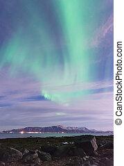 Green Aurora Borealis over mountains outside Reykjavik, Iceland