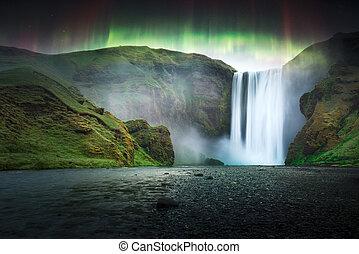 Green aurora light behind famous Skogafoss waterfall on...
