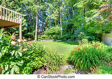 Green back yard with porch and flowers.