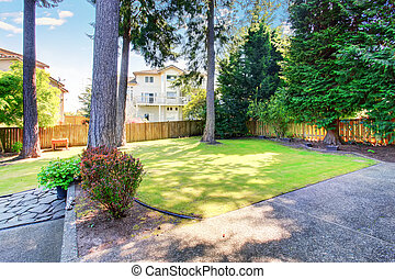 Green backyard garden with trees and well kept lawn.
