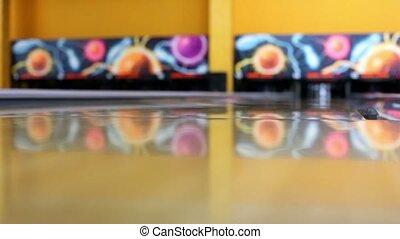 Green ball rolls and beats skittles at bowling lane