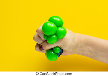 Green ball toy anti-stress in the girl's hand, close-up