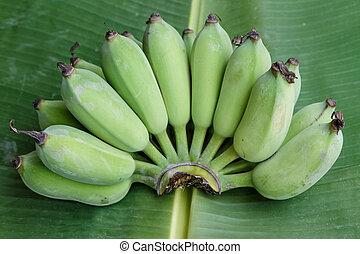 green banana on banana leaf background
