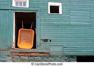 Green barn and yellow wheelbarrel