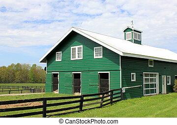 Green barn with farm fencing