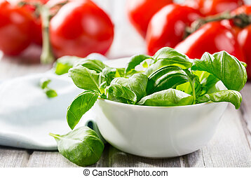 green basil leaves on a bowl and tomatoes