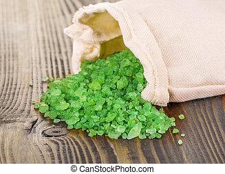 green bath salt in bag on wooden surface