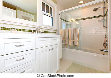 Green bathroom with tub and white cabinets