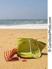 Green beach bag, pink straw hat and starfish