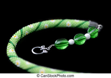 Green beaded necklace with flower print isolated on a black background close up