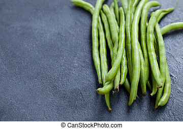 Green beans on grey stone background. Copy space.