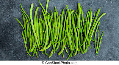 Green beans on grey stone background. Top view.