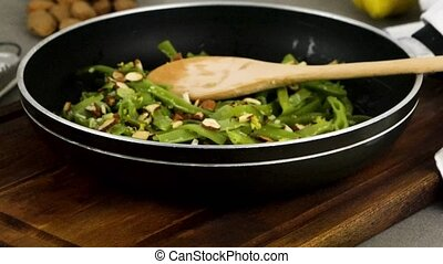 Green beans with roasted almonds on fry pan on kitchen...
