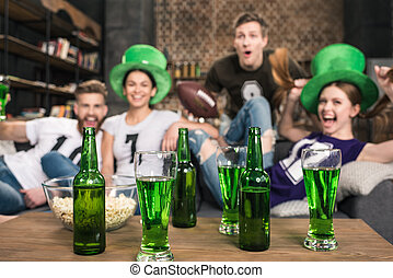 Green beer in bottles and glasses near friends