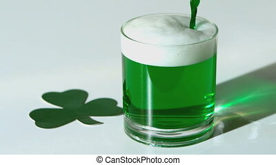 Green beer pouring into a tumbler beside paper shamrock in...