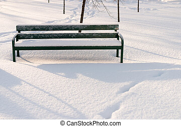 Green bench in a park covered with snow