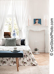 Green bench in front of patterned bed with pillows in white bedroom interior with poster. Real photo