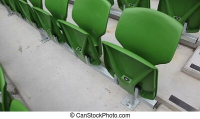 Green benches of the stadium teraccing, moving camera