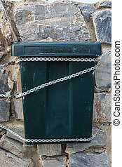 bin tied to a stone wall