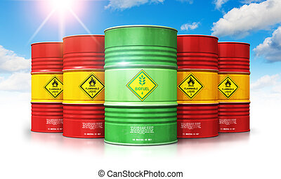 Green biofuel drum in front of red oil or gas barrels against blue sky with clouds and sunlight