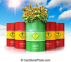 Green biofuel drum with sunflowers in front of red oil or gas barrels against blue sky