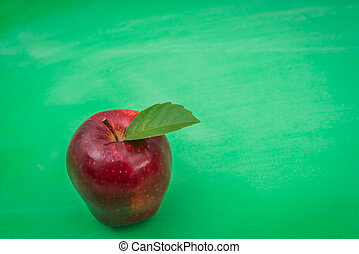Green blank chalkboard with red apple .