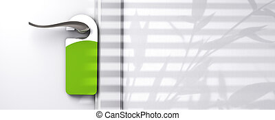 green blank plastic door hanger fixed onto a knob, wall with...