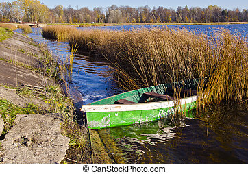 green boat in autumn lake