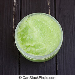 green body scrub on the black wooden background