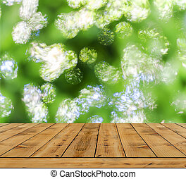 Green bokeh abstract light background, a lot forest bokeh with wood table