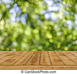 Green bokeh abstract light background, a lot forest bokeh with wooden table