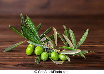green branch of olive tree with berries on wooden background, rustic style