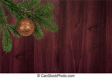 green branch with christmas ball on wooden background