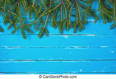 green branches of needles on a blue background from shabby boards