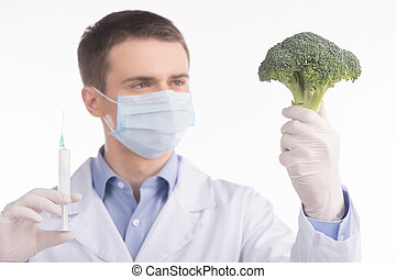 green broccoli in genetic engineering laboratory. man holding broccoli and needle on white background